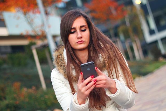 žena s mobilem v ruce