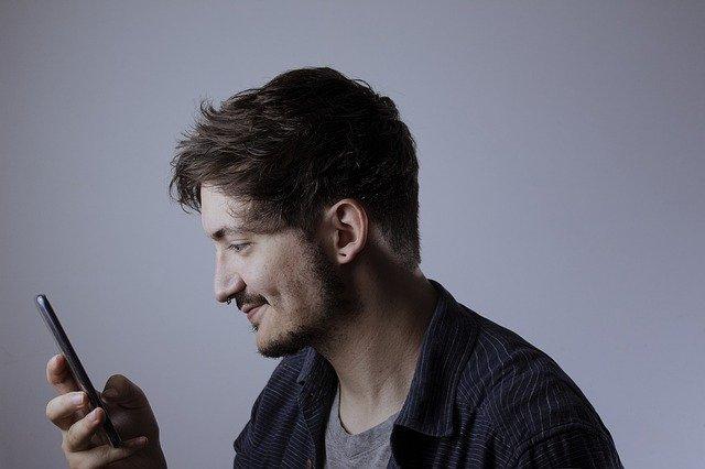 Muž se dívá na telefon
